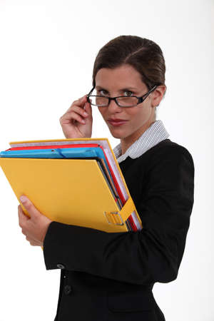 perceptive: Secretary holding a binder and peering over her glasses
