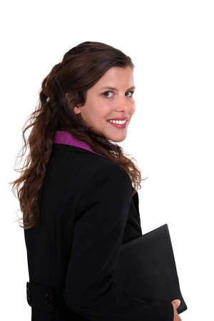 Brunette woman holding folder under arm photo