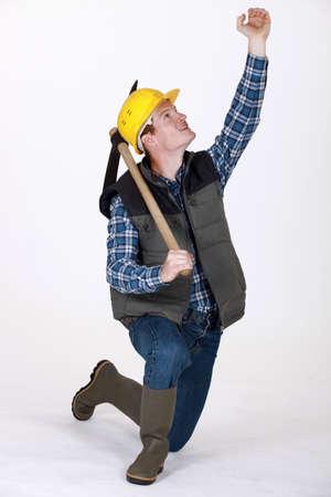 pickaxe: bricklayer holding pickaxe looking upwards
