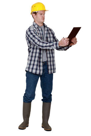 work boots: Incredulous tradesman looking at a clipboard Stock Photo
