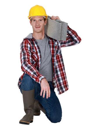 originator: Mason resting breeze block on shoulder