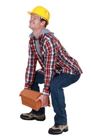 excruciating: Tradesman lifting a heavy load