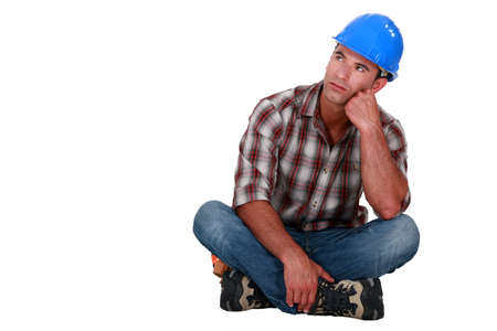 A pensive construction worker sitting on the floor. Stock Photo - 14194485