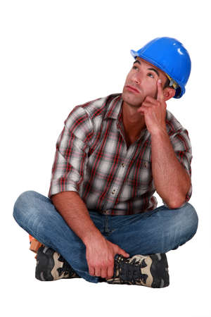 pensive laborer sitting on white background