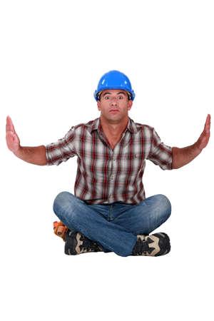 kooky: craftsman sitting on the floor, hands up Stock Photo