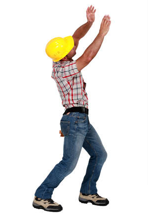 invisible object: Tradesman lifting an invisible object Stock Photo