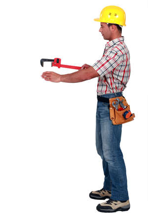 pull along: Tradesman using a pipe wrench to help drag and place an object Stock Photo