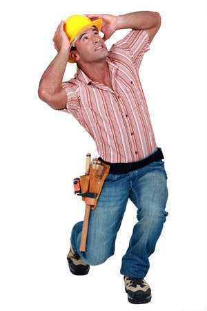 people looking up: A construction worker afraid of something falling. Stock Photo