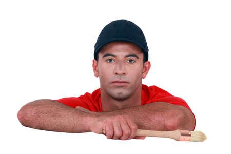 unemotional: Bored man holding a paintbrush Stock Photo