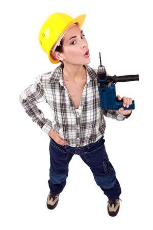 taladro: Un trabajador de la construcción femenina con un taladro como una pistola.