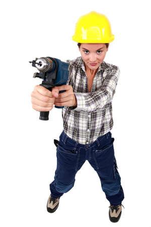 vindictive: Tradeswoman holding a power tool Stock Photo