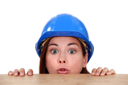 investigative: Female builder peering over ledge Stock Photo