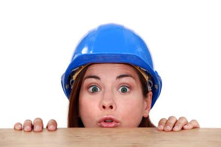 intrusive: Female builder peering over ledge Stock Photo