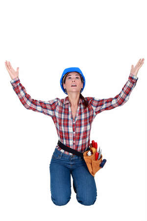 gratified: craftswoman kneeling and raising hands Stock Photo