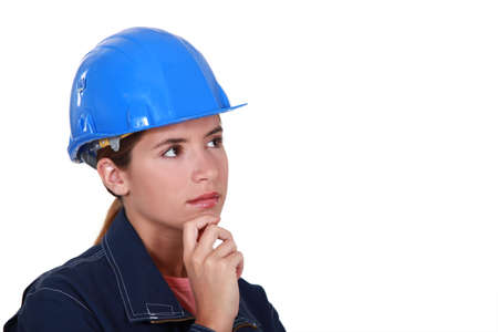female construction worker: A thoughtful female construction worker.