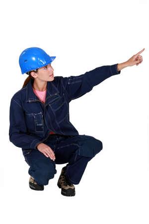 workwoman: Tradeswoman pointing sideways
