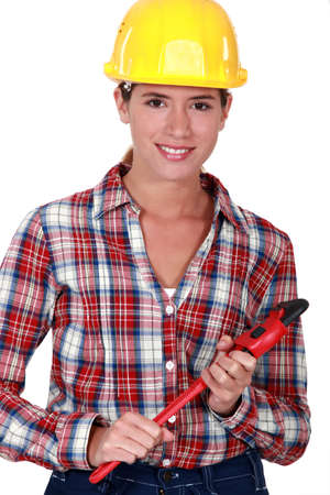 workwoman: Smiling tradeswoman holding a pipe wrench Stock Photo
