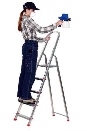 Woman painter using a spray