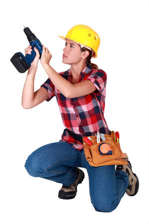 electric drill: Woman carpenter using screwdriver Stock Photo