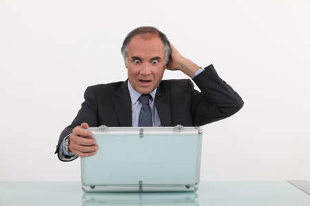 guilty pleasure: Shocked businessman opening case Stock Photo