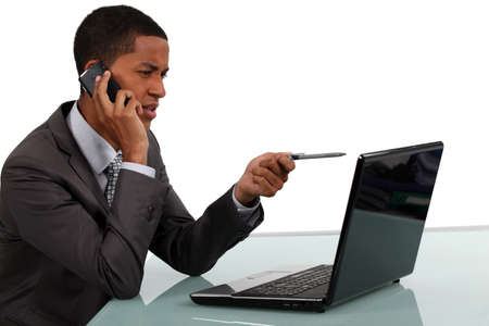 Businessman with phone and laptop photo