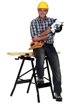 soffit cladding: Man perched on work bench Stock Photo