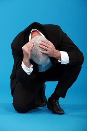 adult crying: Businessman holding his head in despair