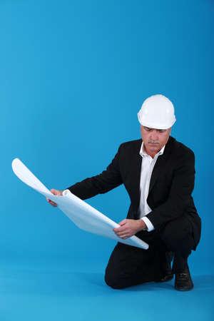 mature architect with blueprints photo