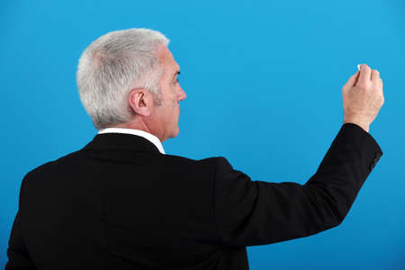 Businessman writing on an invisible board photo