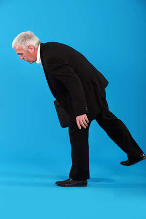 Old businessman struggling to stay in his feet photo