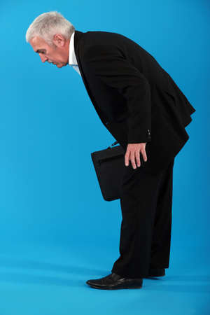 bending over: Tired businessman stooping over