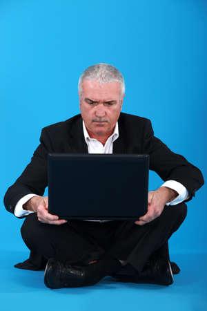 Senior businessman sat on the floor with laptop photo
