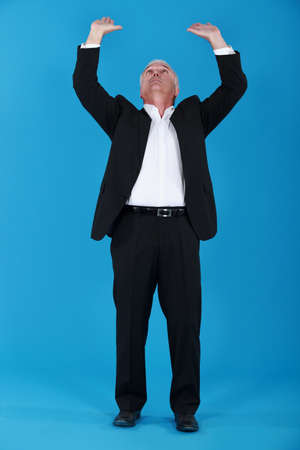 Senior businessman pushing upwards Stock Photo - 14195460