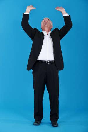 Senior businessman pushing upwards Stock Photo - 14195460