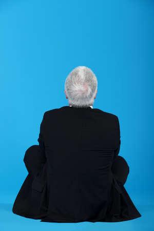position d amour: homme d'âge moyen en position du lotus, le dos tourné à la caméra