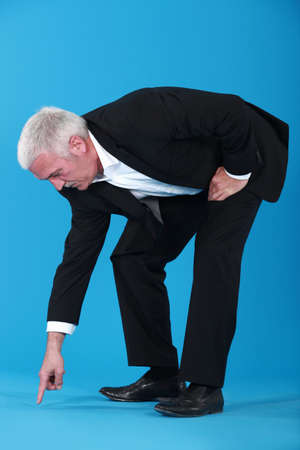 bending over: mature businessman pointing et something on floor