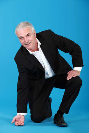 arrodillarse: Hombre de negocios de tocar el piso Foto de archivo