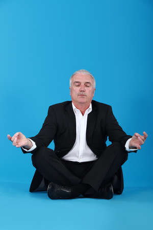 Businessman sitting in a lotus position photo