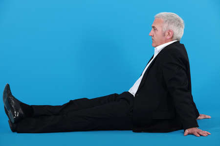 Profile of senior businessman sat on the floor photo