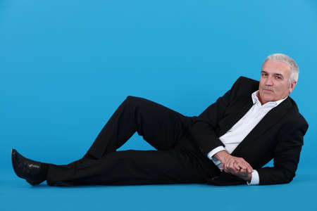 lay down: Grey-haired businessman laying on the floor