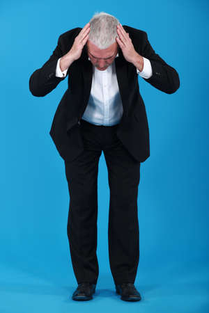 bent over: Businessman staring at the ground