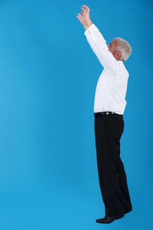 tiptoe: Man stretching to reach an object