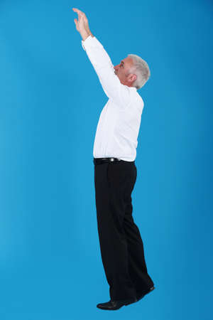 rise to the top: Man with arms up on blue background Stock Photo