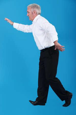 Senior businessman walking along invisible tight-rope