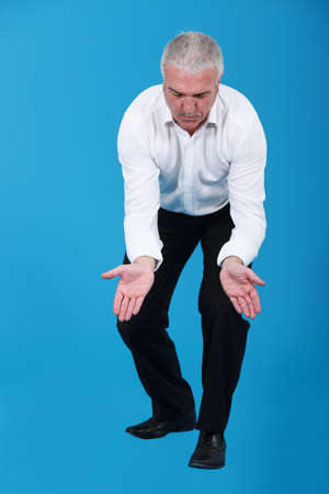 businessman kneeling and holding his hands wide open photo
