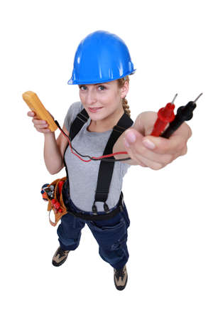 multimeter: female electrician holding a measurement tool