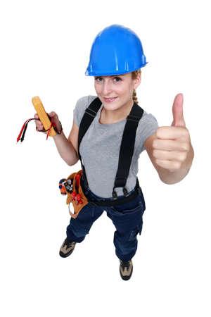 high angle shot: female electrician thumb up