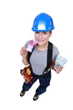 tradeswoman: Tradeswoman holding money