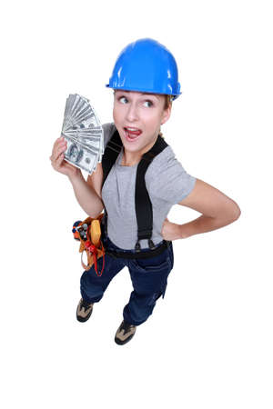 female electrician holding bunch of dollars photo