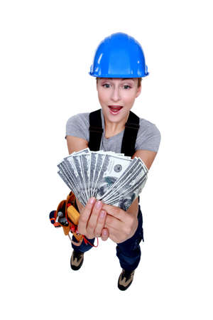 prejudiced: young craftswoman elated over bunch of dollars Stock Photo